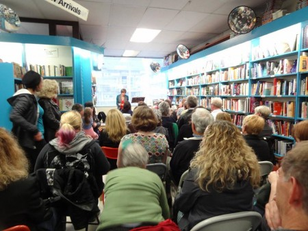 The assembled masses at The People's Co-Op Bookstore listen raptly to Stella Harvey's reading.